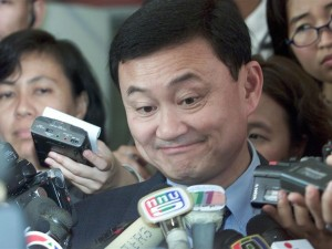 THAKSIN REACTS ON THE FIRST DAY OF HIS TRIAL IN BANGKOK.