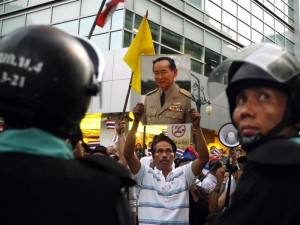 A pro-government supporter holds up a portrait of Thailand's King Bhumibol in Bangkok